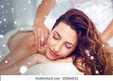 Snow against smiling brunette getting back massage