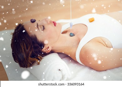 Snow against woman being hypnotized with stones on her body