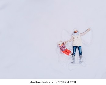 Snow angel shows. Mom and daughter lie in drift, making figures, waving their hands like bird. View top drone.