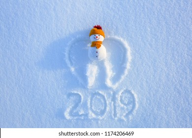 Snow angel with wings in yellow hat and scarf is laying on the snow. Writing 2019. Happy new year. Fabulous winter background for a leaflet.