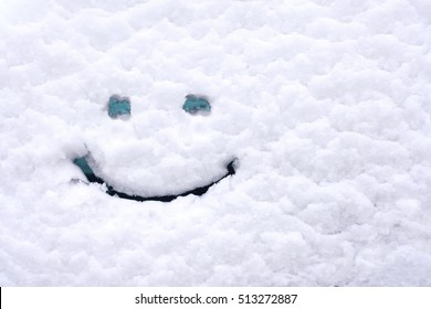 Snow background. Texture of wet snow with a cheerful smiley symbol pattern in the winter window of the car outdoors close-up. Smile in the snow, happy cheerful image.