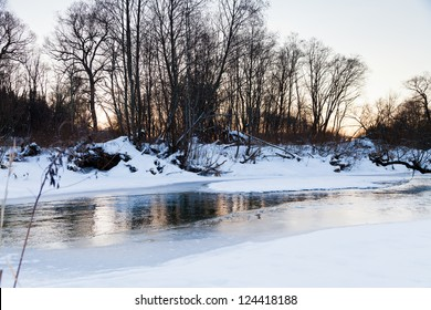 snow banks of forest river at winter sunset