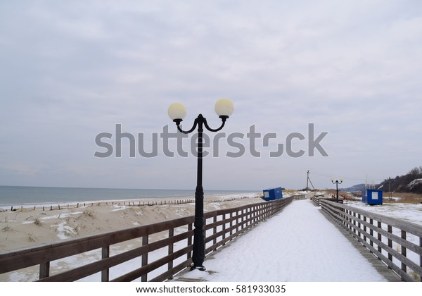 Snow beach and promenade near the sea in winter in Europe