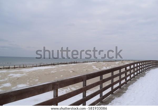 Snow beach and promenade near the sea in winter in Europe