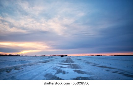 Snow blowing across a gravel back road dividing agriculture snow covered fields in a barren winter landscape at sunset