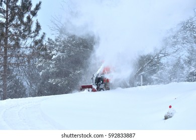 Snow blowing (man cleaning driveway after a snow storm)