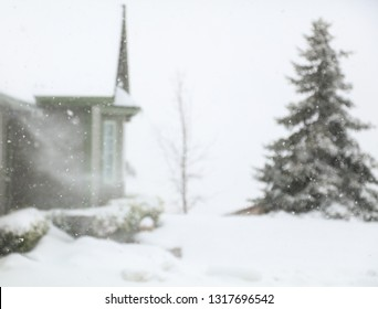 Snow is blowing off of a house roof in a blizzard.  This is an intentional blurred background ready for text.blur
