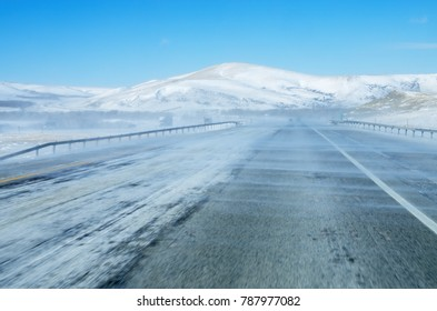 snow blowing on interstate 80 highway in Wyoming reducing visibility with blue sky above