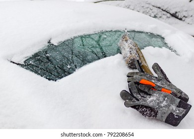 Snow brush and winter gloves on the snow covered rear window of the car