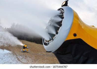 Schneekanonen produzieren Kunstschnee auf einer alpinen Skipiste