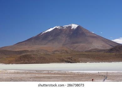 snow cap mountain in high altitude atacama desert in bolivia with lagoon