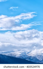 Snow caped mountain range under a blue cloudy sky. Vertical composition
