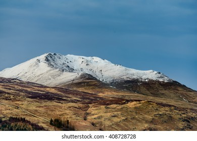 Snow capped Beinn Ghlas and Ben Lawers in late evening sunlight Killin, Scotland