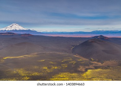 Snow- capped Mount Bolshaya Udina, volcanic massive, one of the volcanic complex on the Kamchatka Peninsula in the far east of Russia. Black sand in the first plan.