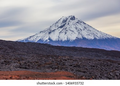Snow- capped Mount Bolshaya Udina, volcanic massive, one of the volcanic complex on the Kamchatka Peninsula in the far east of Russia. Fresh lava field in the first plan.