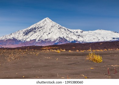 Snow- capped Mount Ostry Tolbachik, the highest point of volcanic complex on the Kamchatka Peninsula in the far east of Russia. Black, volcanic sand in the first plan.