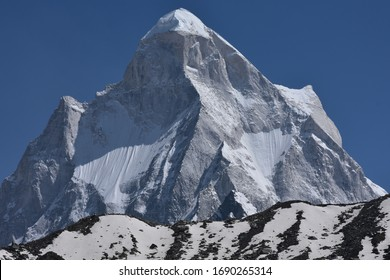 Snow capped mountain peaks of Himalayas touching the blue sky.
