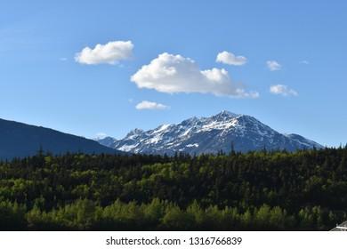 A snow capped mountain peaks over a hill near Skagway Alaska