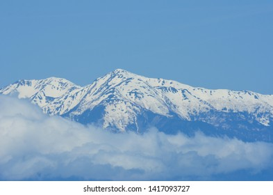 Snow capped mountain peaks are seen against a clear blue sky. Blue the snow-line are soft white clouds. The photograph is in tones of blue.
