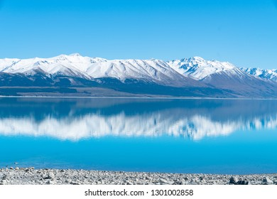 Snow capped mountains reflected in tranquil scenic Lake Pukaki in Mackenzie Basin Canterbury,NZ