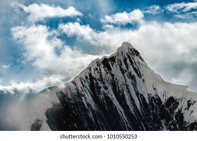Snow Capped Peak of Kawagarbo or Kawa Karpo (also transcribed as Kawadgarbo, Khawakarpo, Moirig Kawagarbo, Kha-Kar-Po or Kawagebo Peak) under a cloudy stormy sky between Yunnan and Tibet, China