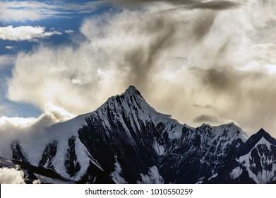 Snow Capped Peak of Kawagarbo or Kawa Karpo (also transcribed as Kawadgarbo, Khawakarpo, Moirig Kawagarbo, Kha-Kar-Po or Kawagebo Peak) under a cloudy stormy sky between Yunnan and Tibet, China