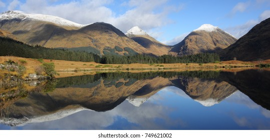 Snow capped summits of Buachaille Etive Mor and Beag reflected in Lochan Urr in Glen Etive in the Scottish Highlands.