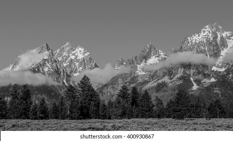 The snow capped Teton Range with fog in the foreground.