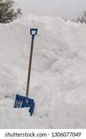 Snow cleaning shovel stuck in a pile of snow, hill.