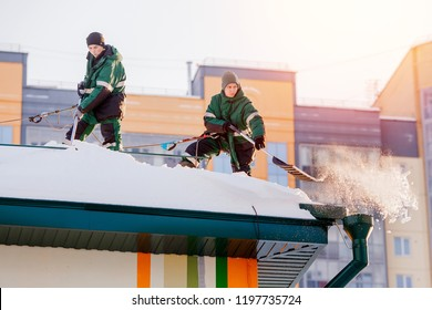 Snow cleaning. Team male workers roof of building from winter with shovels in securing belts of mantra.