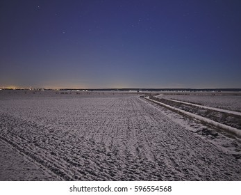 Snow covered agricultural field at Sundom meteor crater in Vaasa, Finland. Night time astrophotography with starry sky.