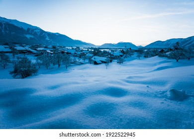 Snow covered alpine winter landscape during blue hour dusk with view over small Austrian traditional village in Wildermieming, Tirol, Austria