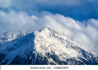 Snow covered Alps peak with cloudy sky background during winter day.
