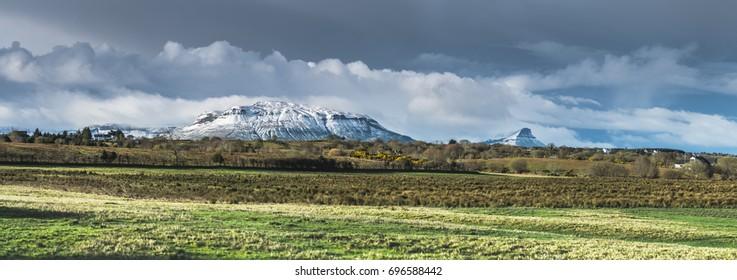 Snow covered Benbulben and Benwisken mountain in front of green field. Irish mountain range in the background. North West Ireland, Darty Mountain Range.  Sligo, Ireland.