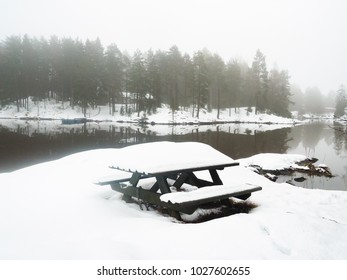 Snow covered bench next to calm lake with reflections from mountain and forest under fog