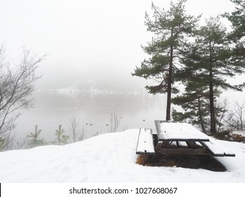 Snow covered bench with table next to misty view, and fog over lake at cold winter
