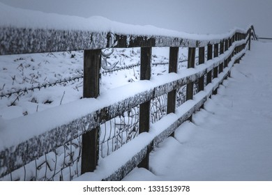 Snow covered border fence across a virgin snowfield.  Snow sticking to the fence a a dark forbidding snow-laden sky
