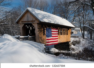 Snow covered bridge has an American flag draped on it to show patriotism. There are plenty of covered bridges in rural New Hampshire. These unique structures are favorite New England attractions.