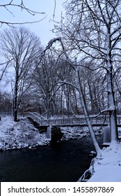A snow covered bridge over the open water of the Pike River in a Wisconsin park early in the winter season in a vertical view.