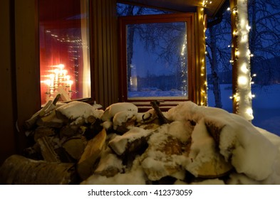 snow covered burch tree firewood logs on christmas decorated house