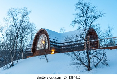 Snow covered cabin (Gabba) designed after the indigenous Sami lavvu (tent). Kirkenes, Norway