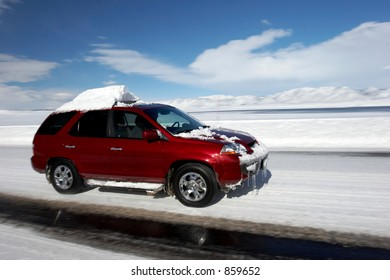 Snow covered car driving in winter on the highway with mountains in the distance. Motion blur added for dynamic picture.