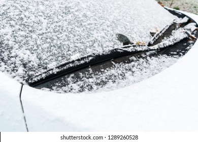 Snow covered car window with wipers, macro, close up. Car wiper blades clean snow from car windows. Flakes of snow covered the car.