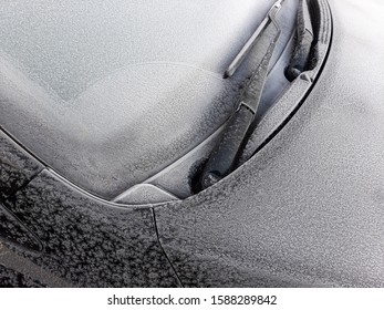 Snow covered car window with wipers, macro, close up