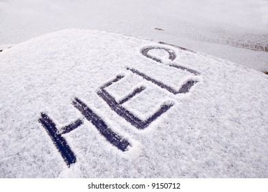 Snow covered car with the word help written on the roof