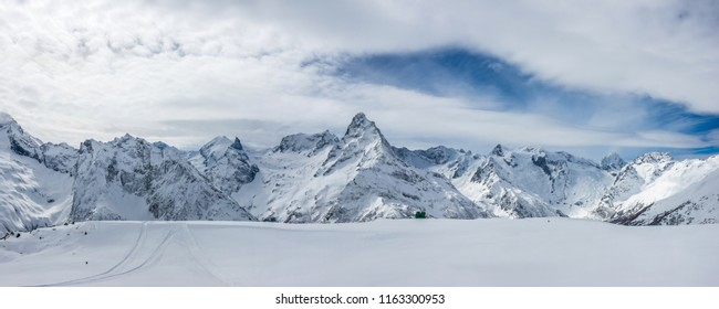 Snow covered Caucasus mountains with Mt. Belalakaya at winter cloudy day. Panoramic view from Mt. Mussa-Achitara slope, Karachai-Cherkess, Russia.