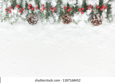 snow covered christmas background with natural fir tree twigs pine cones and red berries