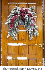snow covered Christmas pine bough decoration with red plaid ribbon on wooden door