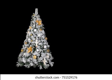 With snow covered christmas tree decorated in white and gold in front of a black background