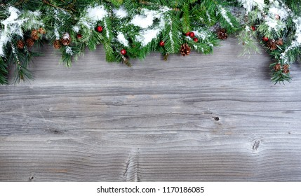Snow covered Christmas tree evergreen branches placed on top of a rustic wooden background